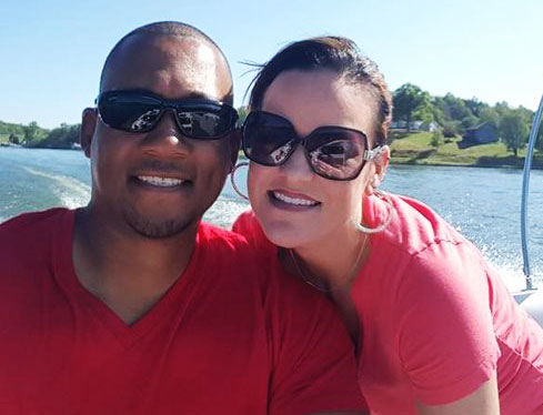 Picture of smiling man and woman on boat wearing red shirts and sunglasses