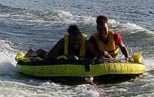 Two females with yellow lifejackets actively tubing on Smith Mountain Lake